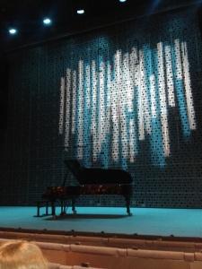 Flygeln väntar på Folke, under en projicerad bild av Eila Hiltunens Sibeliusmonument